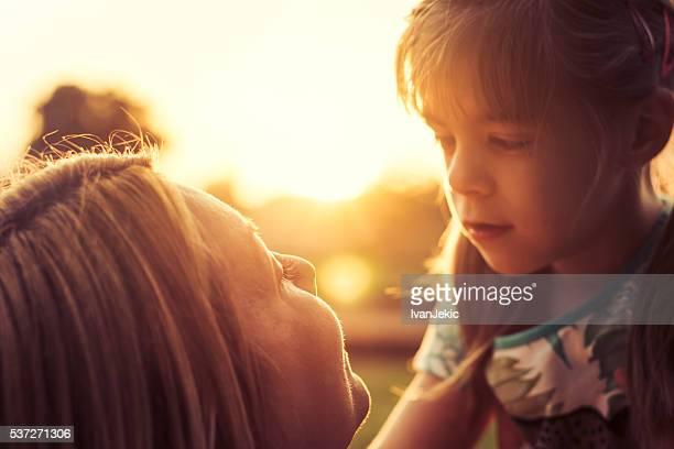 Mother and daughter looking at each other at sunset