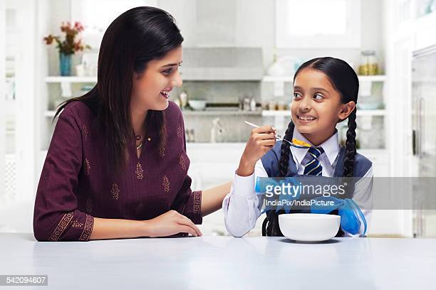 Mother and daughter looking at each other while girl having breakfast
