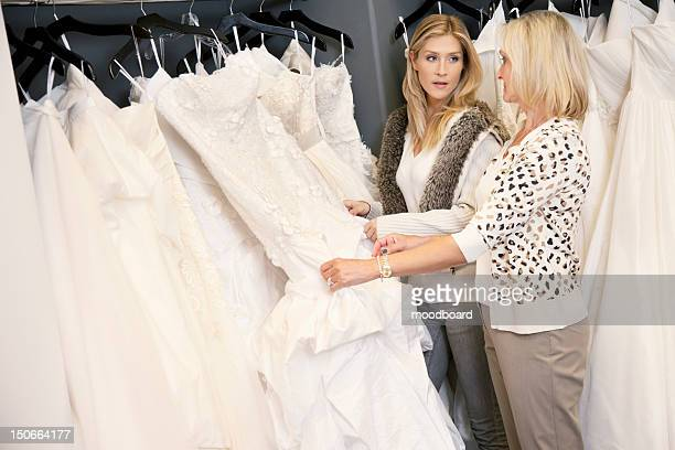 mother and daughter looking at each other while selecting wedding gown in bridal store - wedding dress stock pictures, royalty-free photos & images