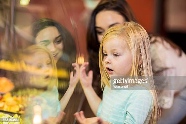 Mother and daughter looking at fruit salad in supermarket