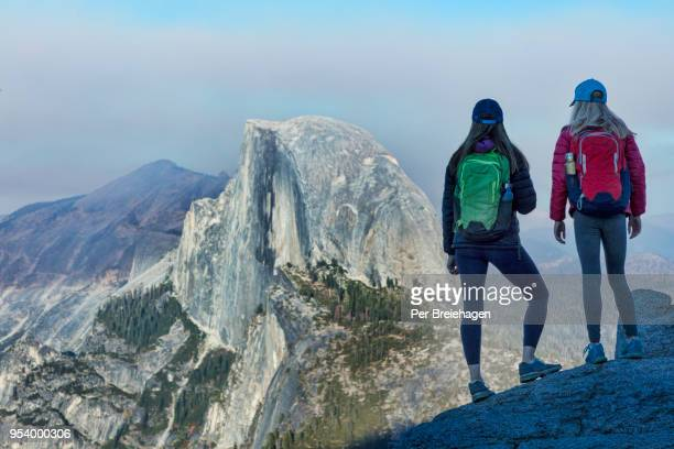 mother and daughter looking at half dome from glacier point - yosemite valley stock photos and pictures