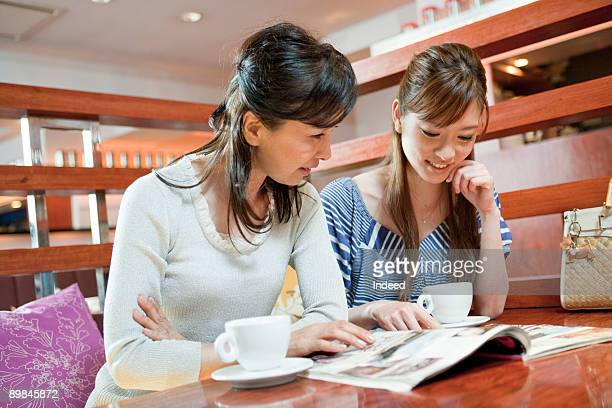 Mother and daughter looking at magazine in cafe