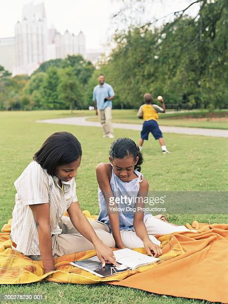 Mother and daughter (11-13) looking at magazine in park