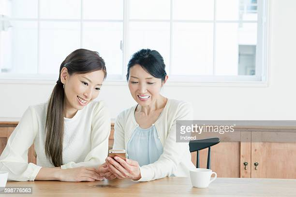 Mother and daughter looking at mobile phone at table