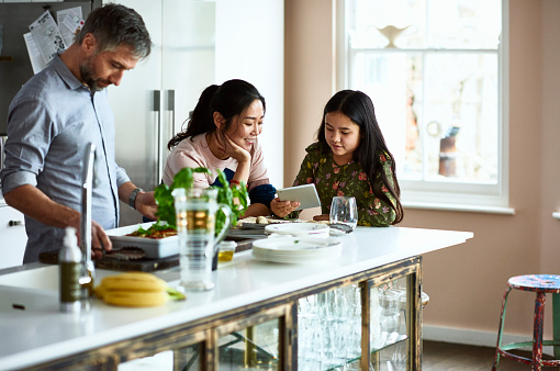 Mother and daughter looking at tablet while father prepares home made meal - gettyimageskorea