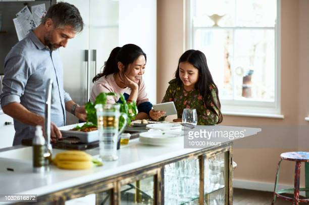 Mother and daughter looking at tablet while father prepares home made meal