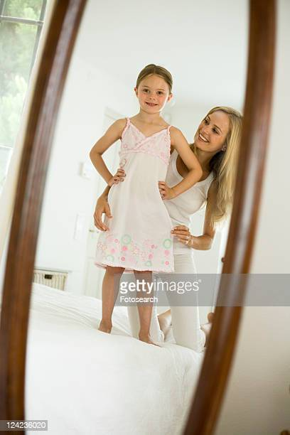 Mother and daughter looking in mirror