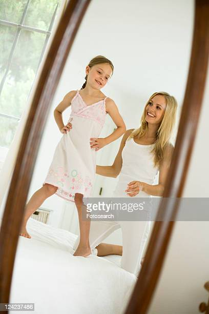 mother and daughter looking in mirror - full length mirror stock photos and pictures