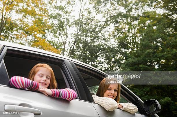 Mother and daughter looking out car window