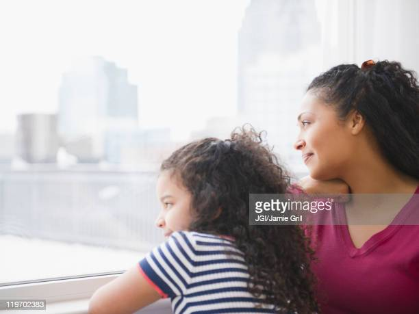 Mother and daughter looking out window