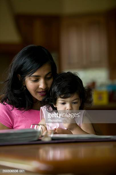 Mother and daughter (3-4) looking through ring binder