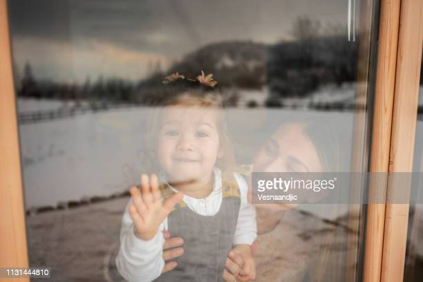 mother and daughter looking through window - finestra foto e immagini stock