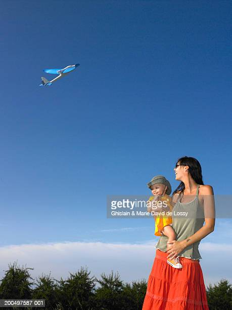 mother and daughter (18-21 months) looking up at toy aeroplane in sky - 18 23 months stock pictures, royalty-free photos & images
