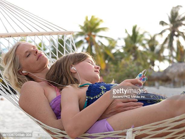 Mother and daughter (12-13) lying in hammock, wearing ear phones, eyes closed