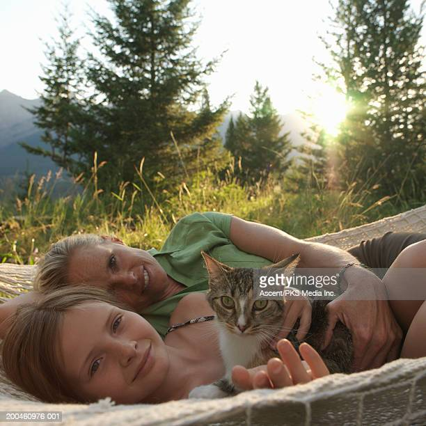 Mother and daughter (9-11) lying in hammock with cat, portrait, summer