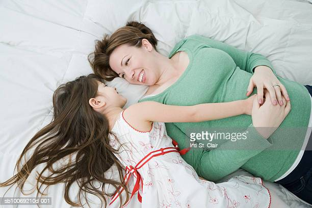 Mother and daughter (4-5) lying on bed, laughing and looking at each other