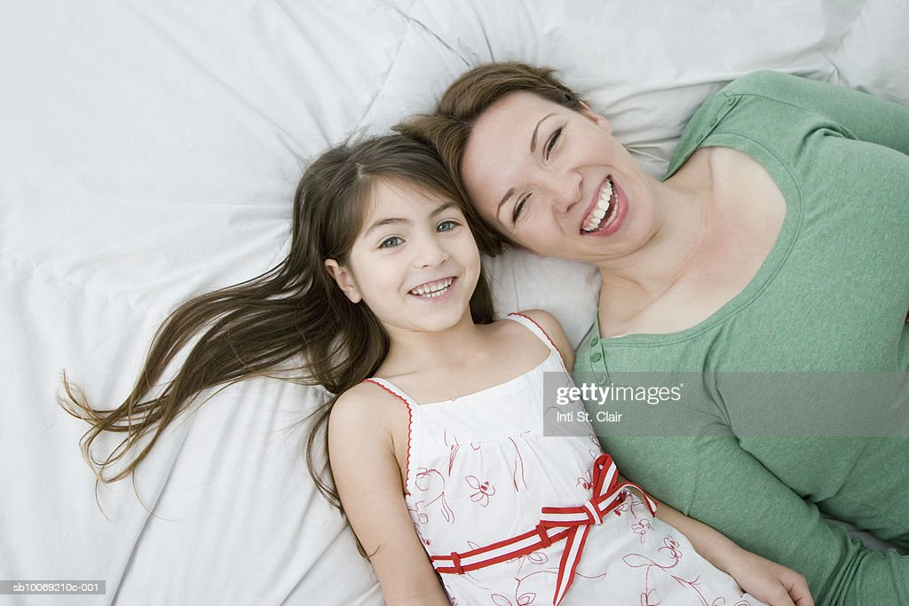 Mother and daughter (4-5) lying on bed, laughing : Stockfoto