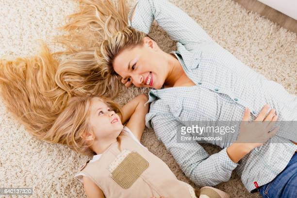 mother and daughter lying on carpet and relaxing - tapijt stockfoto's en -beelden