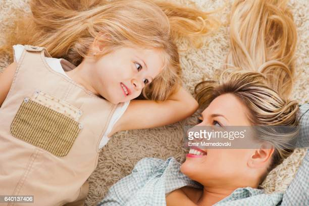 Mother and daughter lying on carpet and relaxing