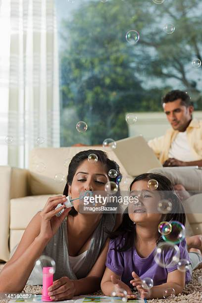 Mother and daughter (6-7) lying on floor and blowing bubbles, father using laptop in background