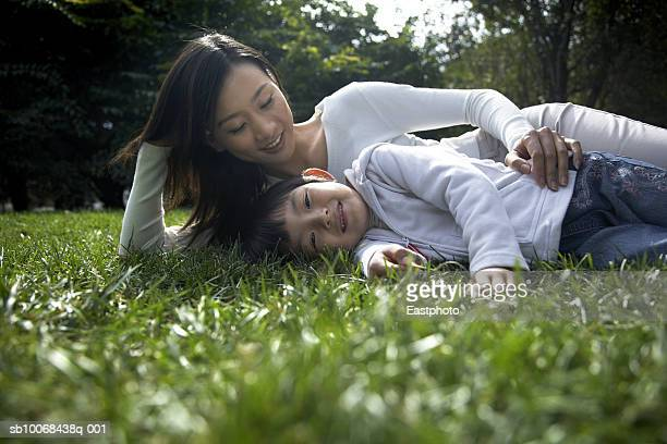 Mother and daughter (4-5) lying on grass in park