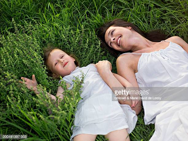 mother and daughter (2-4) lying on grass, smiling, elevated view - saint ferme stock photos and pictures