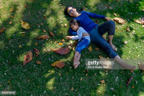 Mother and daughter lying on grass under the big tree