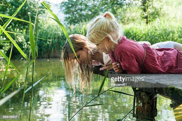 mother and daughter lying on jetty at a lake looking at water - entdeckung stock-fotos und bilder