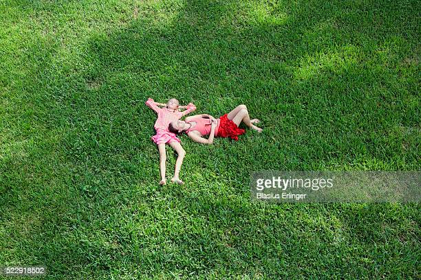 mother and daughter lying on lawn - blasius erlinger stock pictures, royalty-free photos & images
