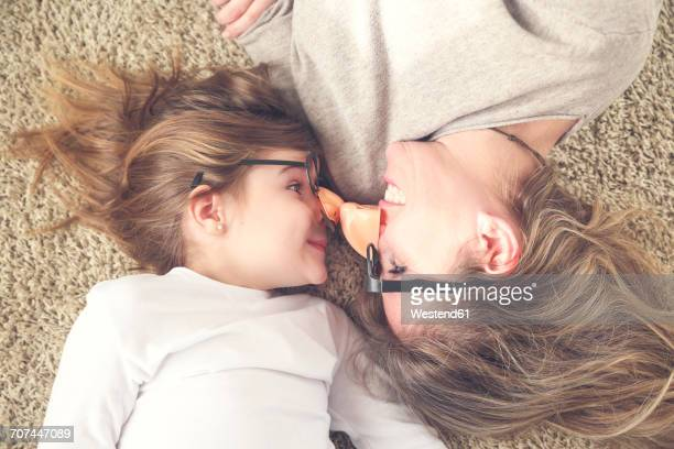 Mother and daughter lying on the carpet wearing funny glasses with plastic nose