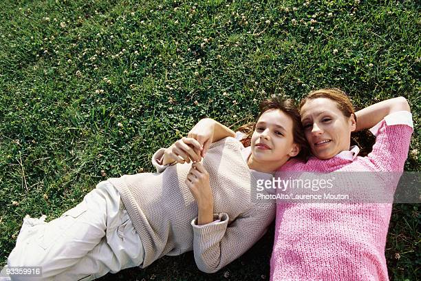 Mother and daughter lying together on grass, smiling at camera
