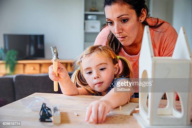 mother and daughter making a bird box - design occupation stock pictures, royalty-free photos & images