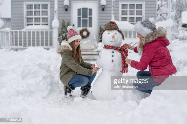 mother and daughter making a snowman in front of the house, during covid-19 - coronavirus winter stock pictures, royalty-free photos & images