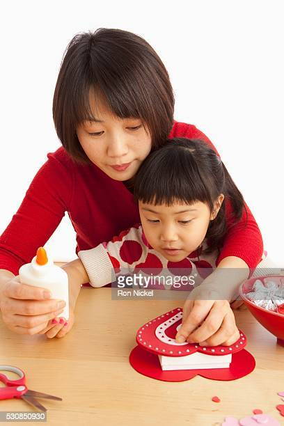 A Mother And Daughter Making A Valentine's Day Craft