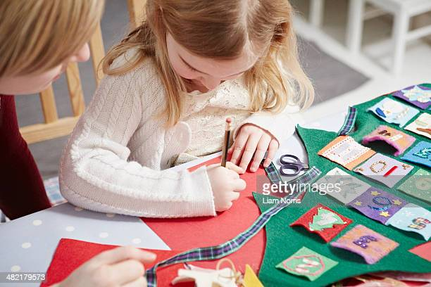 mother and daughter making advent calendar at kitchen table - advent calendar stock photos and pictures