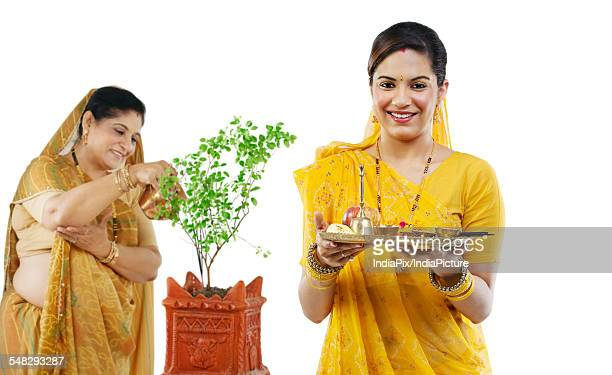 Mother and daughter making an offering
