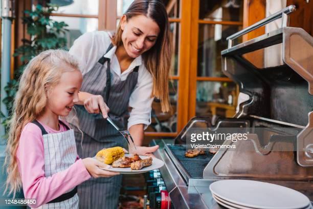 裏庭でバーベキューをする母と娘。 - 網焼き ストックフォトと画像