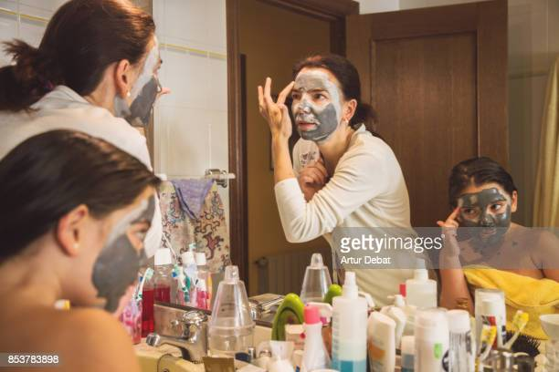 Mother and daughter making beauty treatments with facial mask made of mud with children imitating mother behavior in the bathroom.