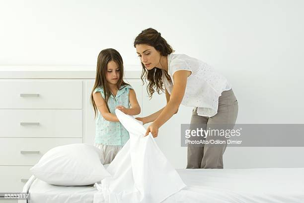mother and daughter making bed together - little girls bent over stock photos and pictures