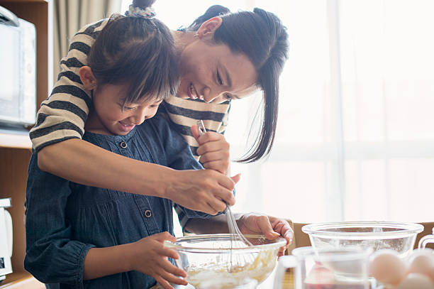 mother and daughter making  cookies together - 焗 預備食物 個照片及圖片檔