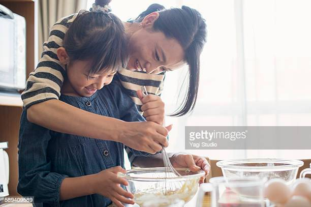 mother and daughter making  cookies together - スイーツ ストックフォトと画像