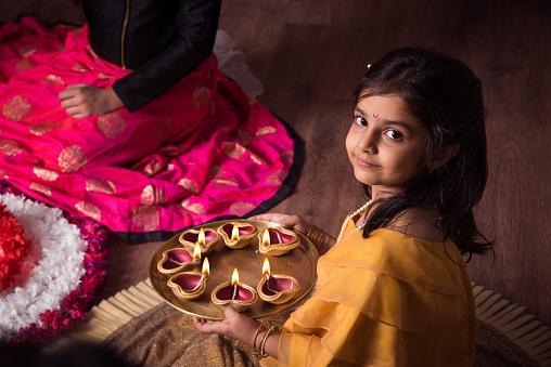Mother and daughter making flower rangoli and girl lighting diya or samai 913623414