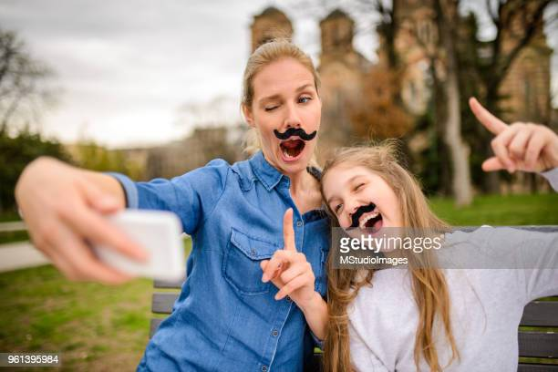 Mother and daughter making funny selfie.