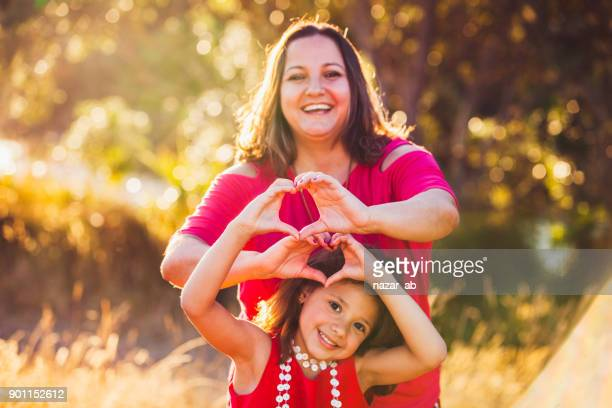 Mother and daughter making heart shape.