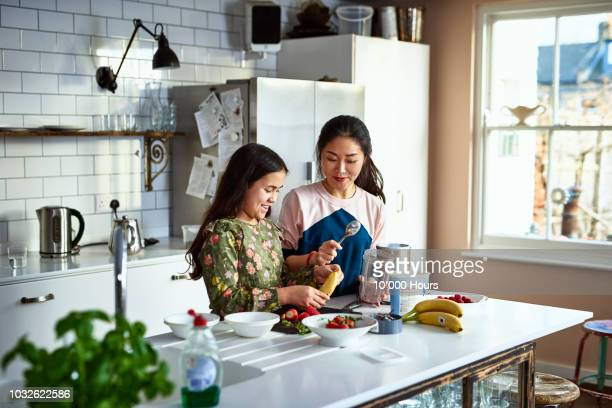 mother and daughter making homemade smoothies in kitchen - stereotypically middle class stock photos and pictures