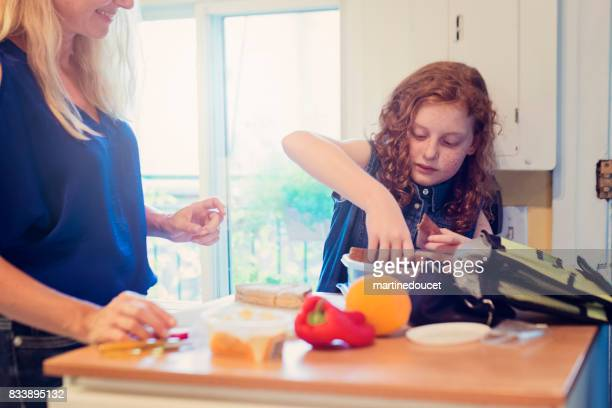 Mother and daughter making lunch on school morning.
