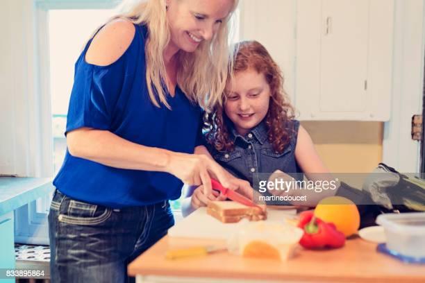 """moeder en dochter maken van de lunch op school ochtend. - """"martine doucet"""" or martinedoucet stockfoto's en -beelden"""