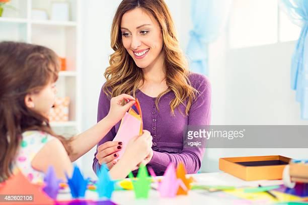Mutter und Tochter machen origami.