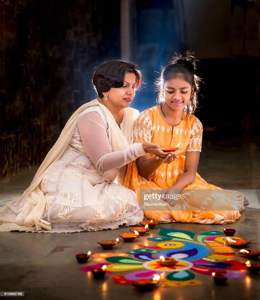 Mother and Daughter making Rangoli, decorating with Diyas for Diwali : Stock Photo