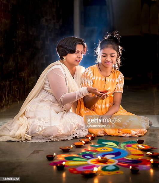 Mother and Daughter making Rangoli, decorating with Diyas for Diwali